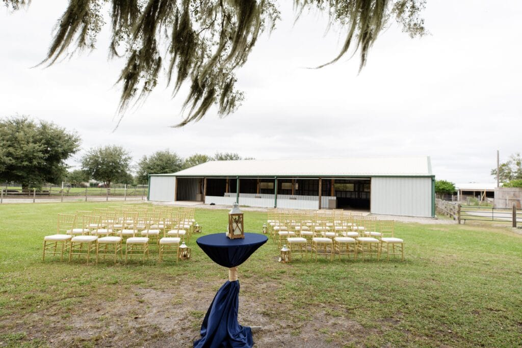 cocktail table with navy blue table cloth in front of rows of white and gold chairs for outdoor wedding ceremony